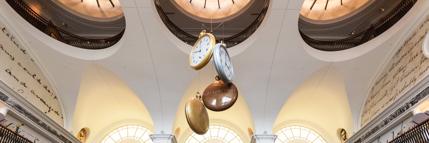 Clocks hanging from a ceiling.